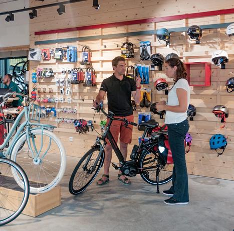 Vendeur cycle conseillant une cliente sur l'achat d'un vélo électrique