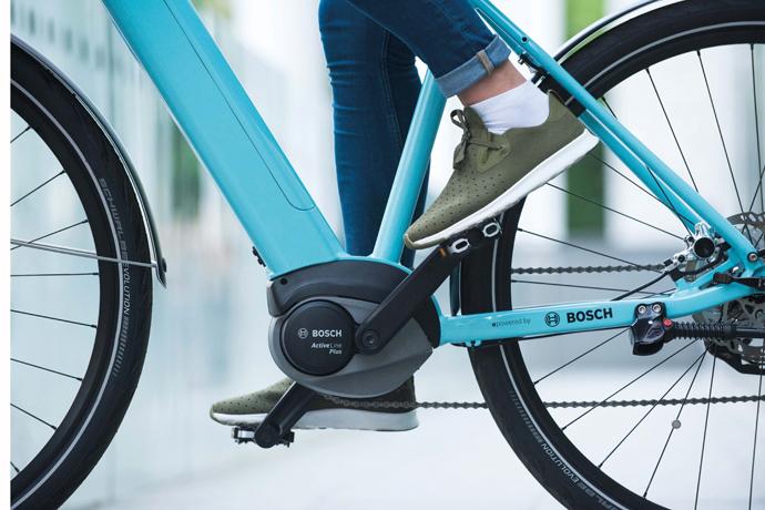 Cycliste qui pédale sur un vélo électrique bleu