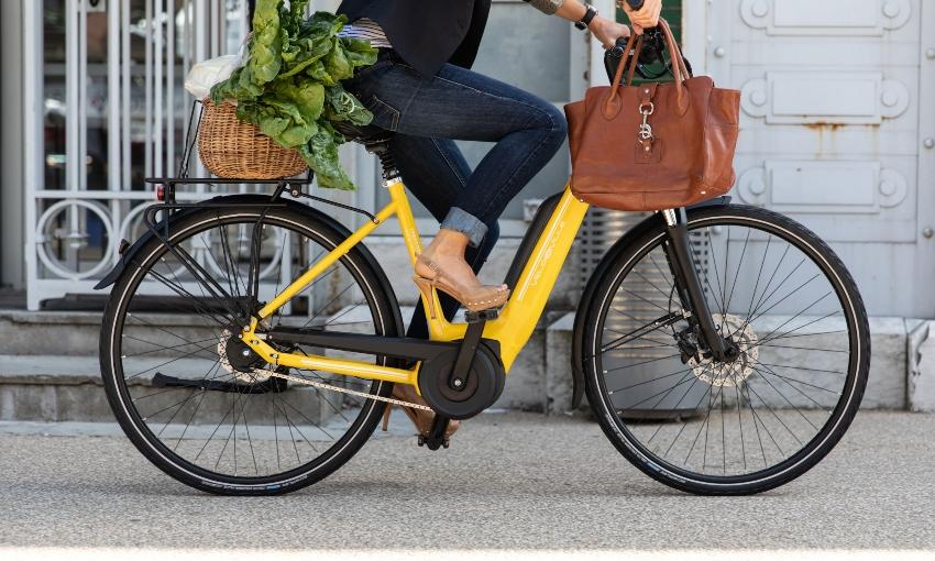Gros plan sur les jambes d'une cycliste pédalant sur un vélo électrique jaune