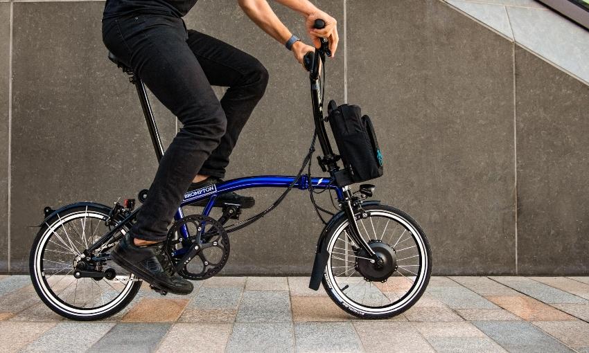 Cycliste pédalant sur un vélo électrique pliant Brompton