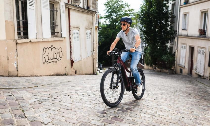 Homme en train de monter une pente à vélo électrique Moustache en ville