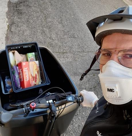 Livreur avec masque sur son vélo cargo pendant le covid