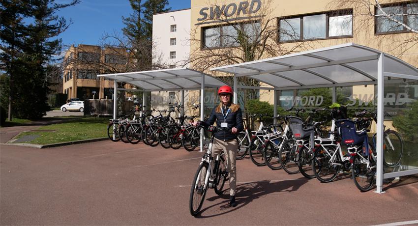 Femme utilisant un vélo de fonction devant le siège de son entreprise
