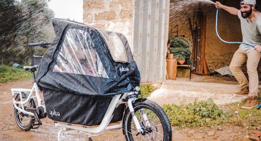 Vélo cargo avec des enfants protégés par la tente de pluie