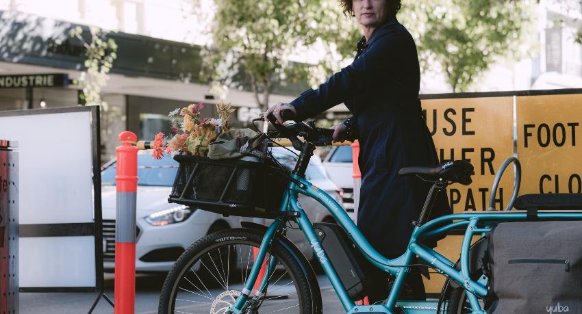 Femme marchant à côté de son vélo cargo chargé avec panier et sacoches