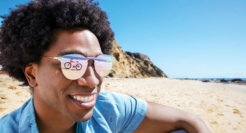 Homme sur une plage avec reflet vélo dans ses lunettes