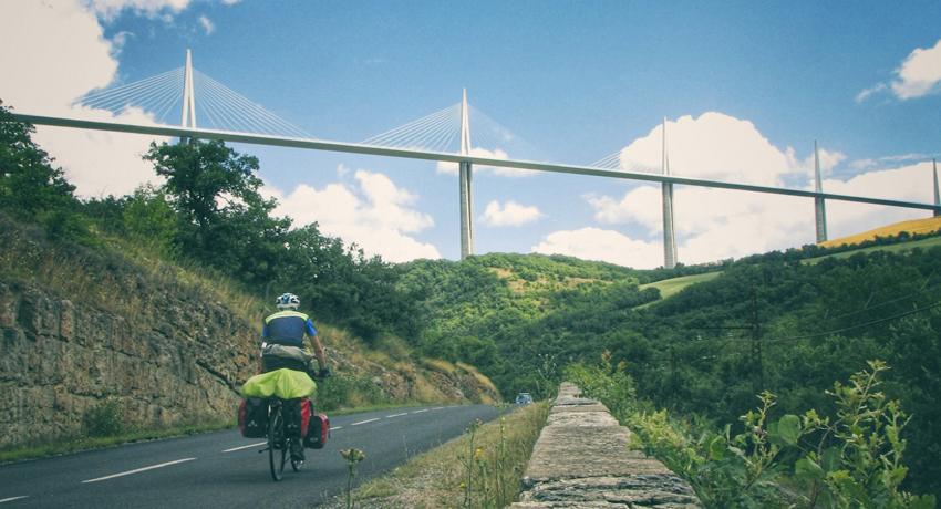 Cyclotouriste devant viaduc de Millau