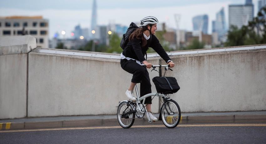 Jeune femme pédalant sur un vélo pliant Brompton souriante