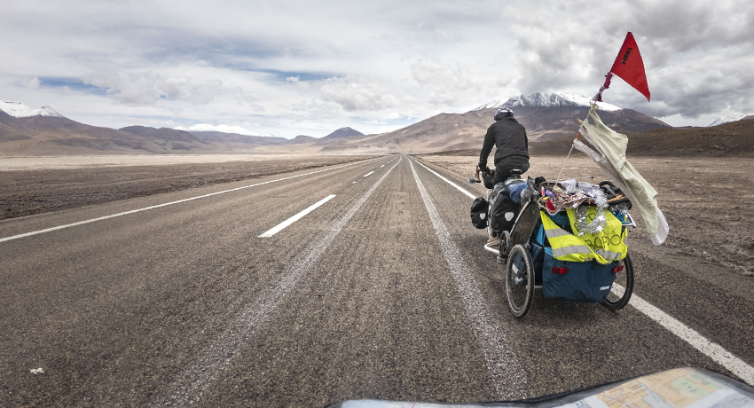 Cyclotouriste tirant une remorque avec son bébé en Amérique du Sud