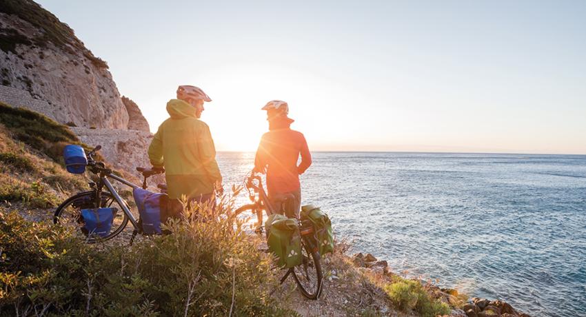 Couple de cyclistes devant coucher de soleil sur la mer