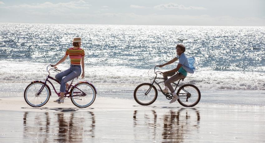 Cyclistes souriants sur des vélos Electra sur une plage
