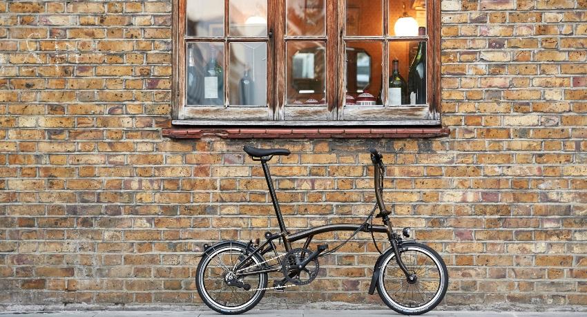 Vélo pliant Brompton devant une fenêtre