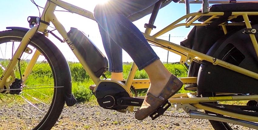Cycliste qui pédale sur un vélo cargo à la campagne