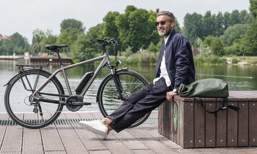Homme souriant assis près de son vélo