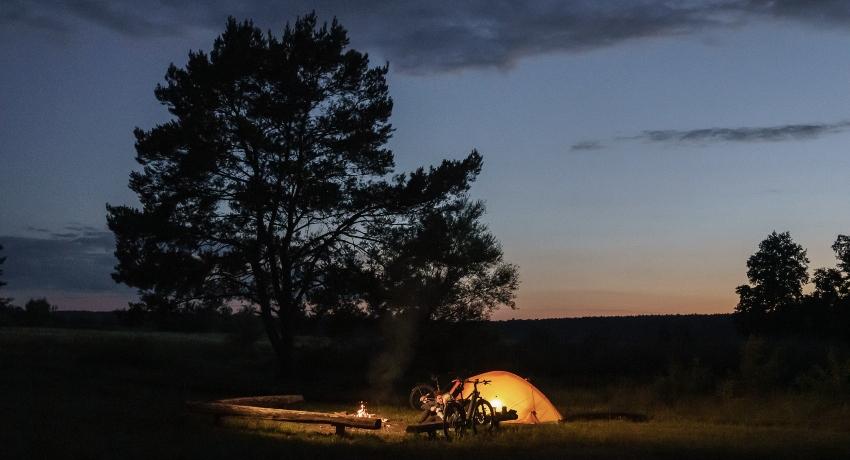 Une tente éclairée de l'intérieur pendant un voyage à vélo