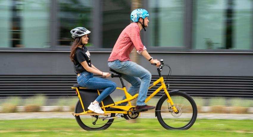 Cycliste transportant une adolescente sur un vélo cargo rallongé