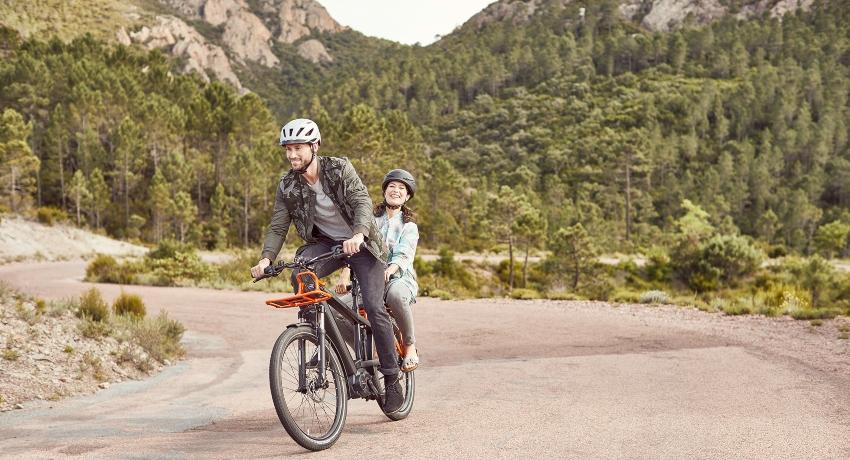 Couple sur un vélo cargo à la montagne