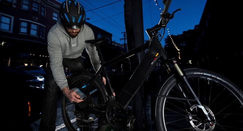 Cycliste qui accroche son vélo avec un antivol Abus la nuit