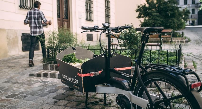Homme en train de décharger une caisse d'un vélo cargo