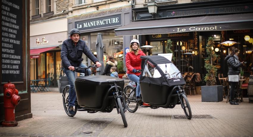Deux cyclistes sur des vélos cargo en ville