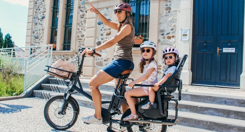 Jeune mère avec ses deux enfants sur un cargobike