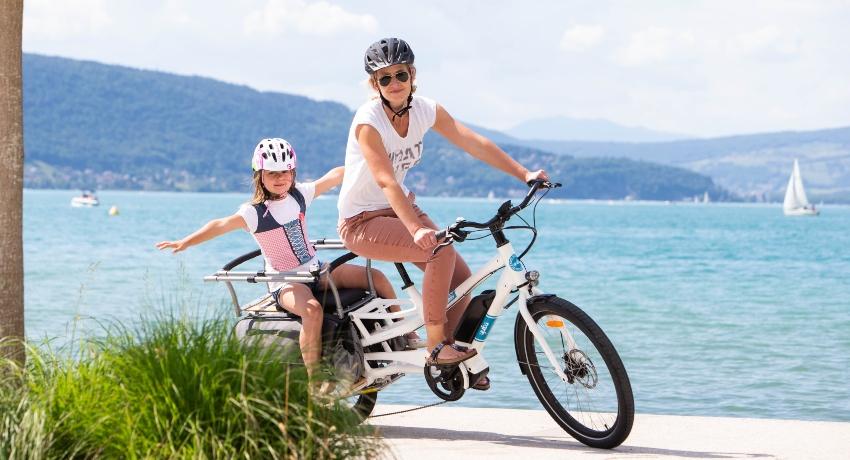Mère et sa fille à vélo cargo devant un lac