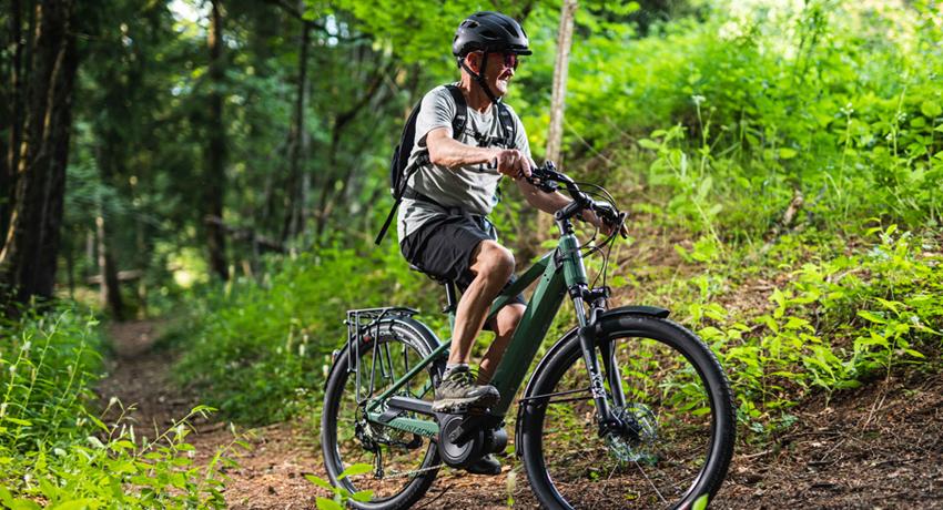 Personne retraitée sur un vélo électrique en forêt