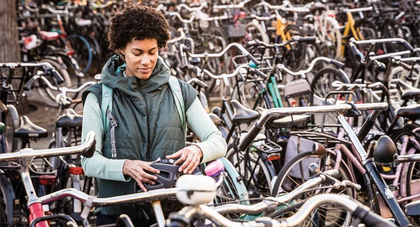 Cycliste mettant son casque dans un garage à vélos