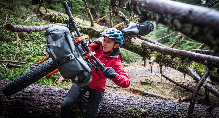 Cycliste femme portant son vélo bikepacking