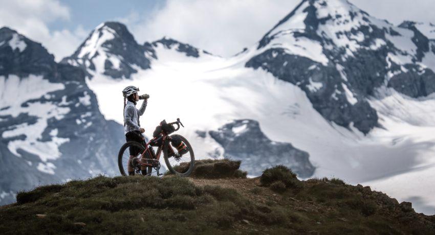 Cycliste et son vélo gravel devant une montagne enneignée