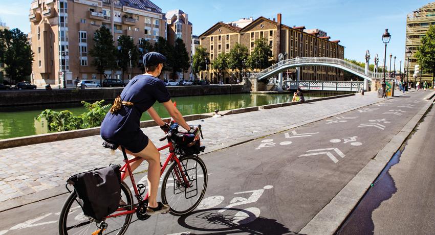 Jeune femme à vélo le long du canal St Martin
