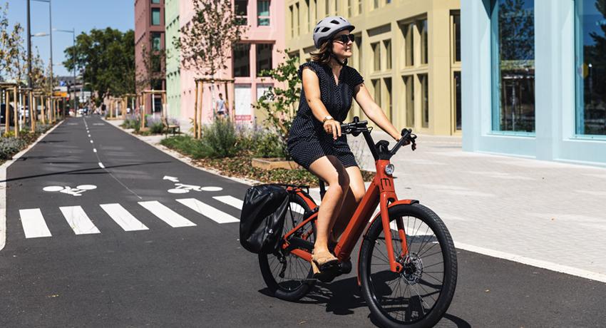 Femme roulant sur un vélo électrique Moustache rouge