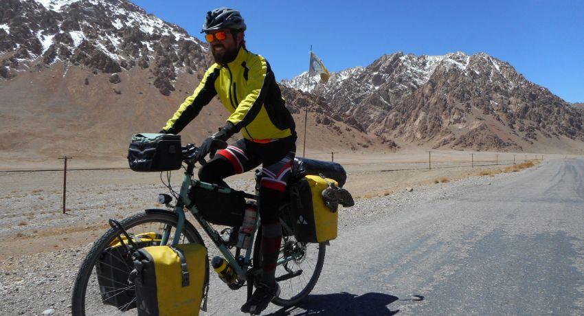 Cycliste pédalant devant des montagnes enneigées