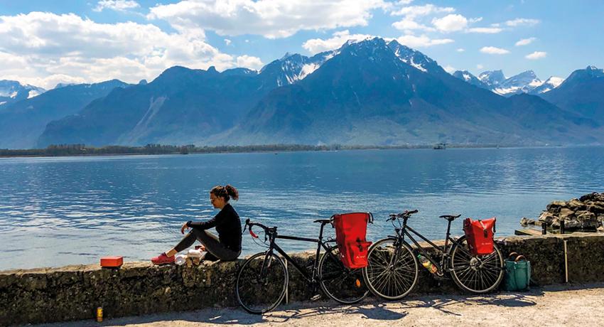 Cycliste à côté de son vélo près d'un lac