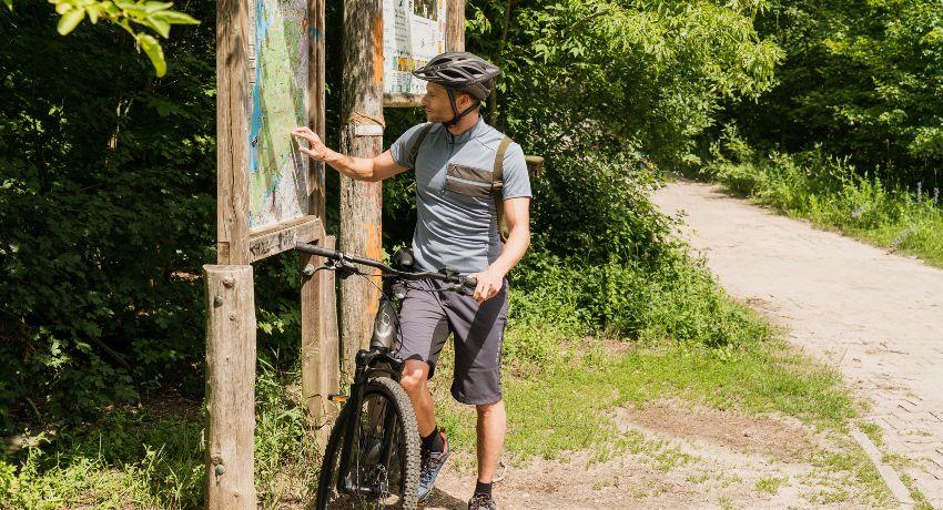 Cycliste à vélo étudiant une carte à la campagne
