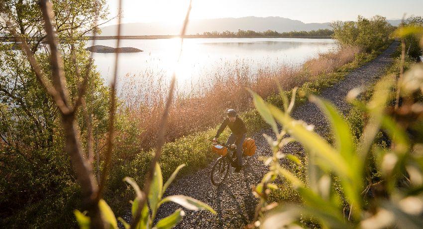 Cycliste roulant en mode slow tourisme le long d'un lac