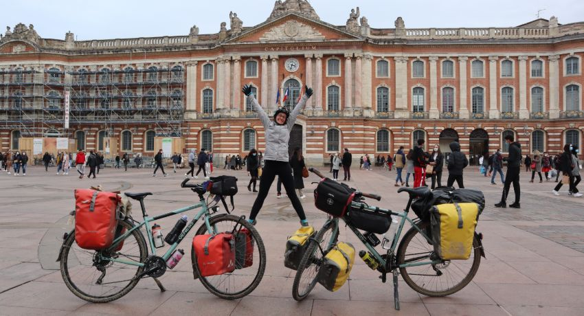 Cycliste rentrant de voyage à vélo devant le Capitole à Toulouse